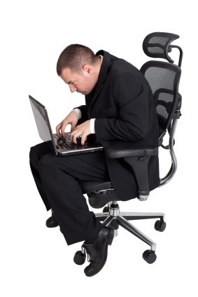 man with bad posture on a laptop