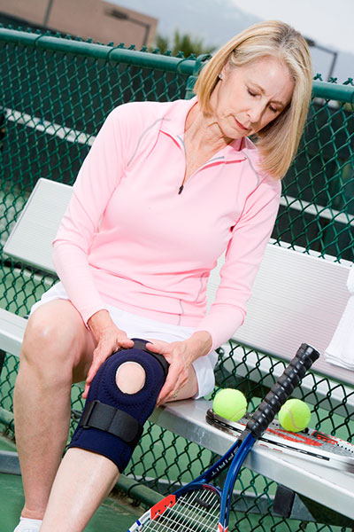woman putting on knee band to play tennis