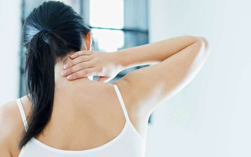 woman holding her neck due to neck pain