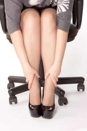 woman is sitting in chair and massaging her tired legs
