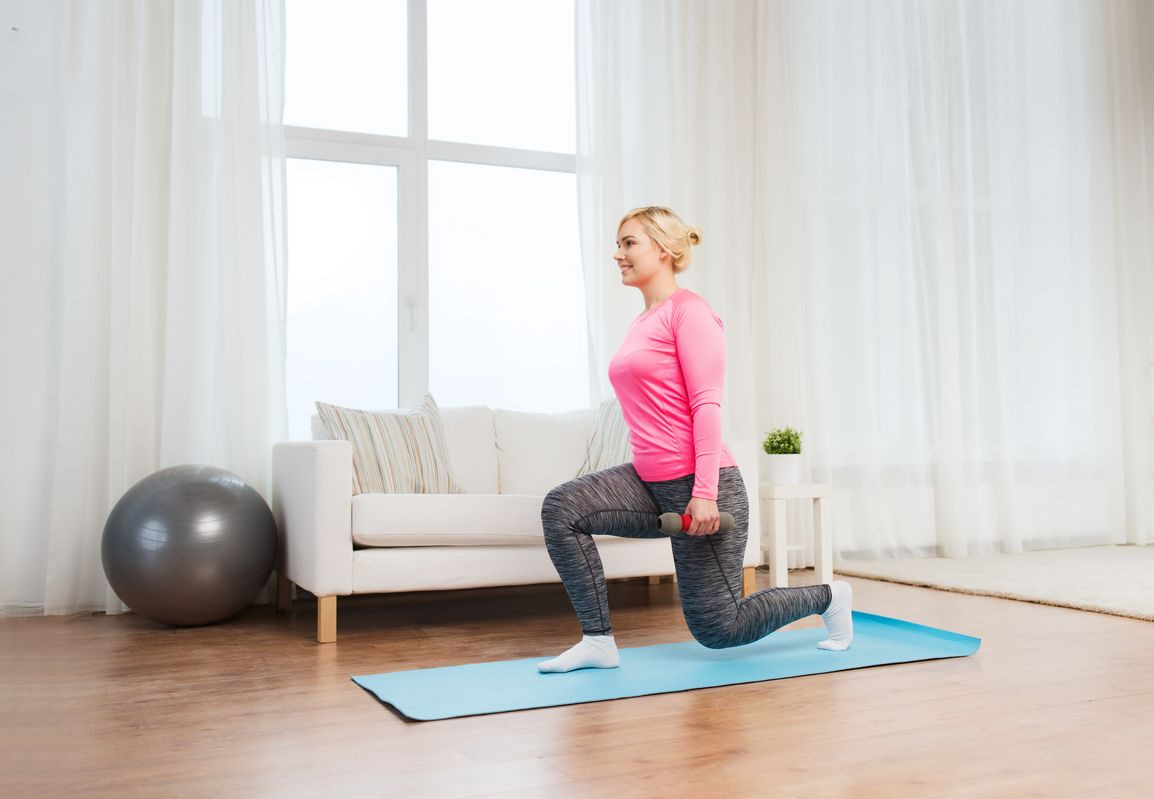 smiling woman with dumbbells exercising and doing squats at home